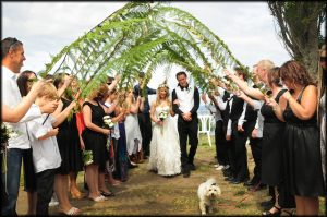 Fern fronds act as an arch to this wedding couple